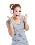 Excited woman listening to headphone Royalty Free Stock Image