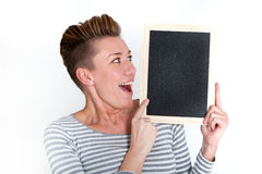 Excited woman looking at a blank tablet. With her mouth open in surprise as she displays the screen to the viewer, on white Stock Photo
