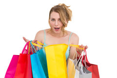 Excited woman looking at camera with many shopping bags. On white background Royalty Free Stock Photography
