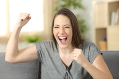 Excited woman looking at camera. Excited woman looking at you sitting on a sofa in the living room at home Stock Images