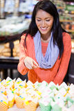 Excited woman looking at cupcakes. In food counter of supermarket Royalty Free Stock Photography
