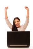 Excited woman looking into laptop computer. Excited woman looking into laptop computer with high raised hands happy of success Stock Photo