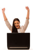 Excited woman looking into laptop computer. Excited woman looking into laptop computer with high raised hands happy of success Royalty Free Stock Photos