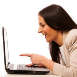 Excited woman looking into laptop computer. Excited woman looking into laptop computer pointing with finger on screen Stock Photos
