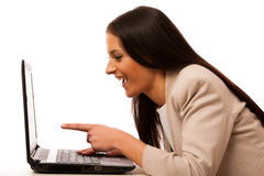 Excited woman looking into laptop computer. Excited woman looking into laptop computer pointing with finger on screen Royalty Free Stock Photos