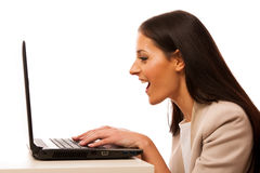 Excited woman looking into laptop computer. Excited woman with surprised expression looking into laptop computer Stock Photography