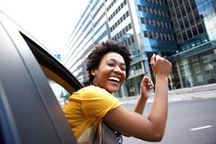 Excited woman looking out the car window with her arms raised. Portrait of cheerful young african woman looking out the car window with her arms raised Royalty Free Stock Photography