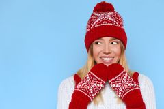 Excited woman looking sideways in excitement. Surprised christmas girl wearing knitted warm hat and mittens, isolated on blue. Excited woman looking sideways in Royalty Free Stock Photo