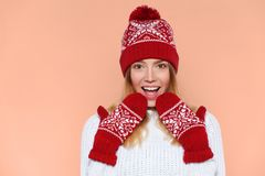 Excited woman looking sideways in excitement. Surprised Christmas girl wearing knitted warm hat and mittens, isolated.  Stock Photos