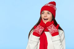 Excited woman looking sideways in excitement. Surprised christmas girl wearing knitted warm hat and scarf, isolated on blue.  Stock Photos