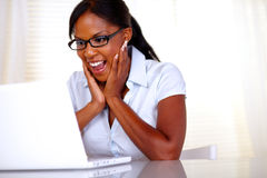 Excited woman looking to laptop screen. With black glasses at workplace - copyspace Royalty Free Stock Images