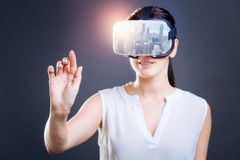 Excited woman looking through virtual mask. Colorful images. Close up of young woman looking through virtual reality mask while putting her finger forward and Stock Photography