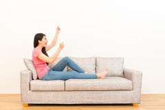 Excited woman looking at the white background. Copyspace area happy raised her hands with fist gestures sitting on the couch at home in the living room on Royalty Free Stock Photos