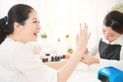 Excited woman love her new done manicure. Excited happy mixed race asian chinese women enjoy love her new done manicure by a manicurist using portable uv light Stock Photo