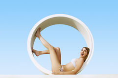 Excited Woman Lying In Tube Shaped Structure At Resort Stock Image