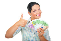 Excited woman with money giving thumbs up royalty free stock photography