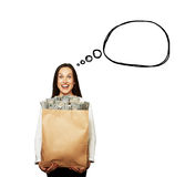 Excited woman with money and speech bubble. Excited young woman holding paper bag with money over white background. concept photo with drawing speech bubble royalty free stock image