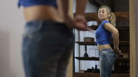 Excited woman in old jeans after losing weight stock video