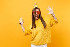 Excited woman in orange funny glasses birthday hat with playing pipe spreading hands, celebrating, enjoying holiday