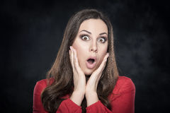 Excited woman over dark background. Studio portrait of surprised woman over dark background Royalty Free Stock Photos