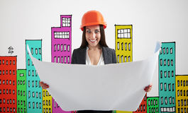 Excited woman over drawing houses. Excited woman in orange hardhat with blueprint over grey wall with variegated drawing houses Royalty Free Stock Images