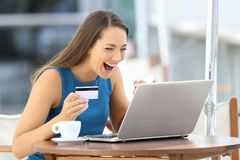 Excited woman paying on line with a credit card. Single excited woman paying on line with a credit card and a laptop sitting in a bar terrace Royalty Free Stock Image