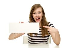 Excited woman pointing at blank sign. Young woman over white background Royalty Free Stock Photo