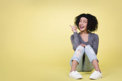 Excited woman pointing at copy-space. Happy woman pointing up at empty copy space being excited, isolated on yellow background Royalty Free Stock Image