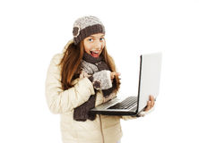 Excited woman pointing at netbook laptop screen. Winter style. Isolated on white background Stock Images
