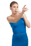 Excited woman pointing up. Attractive young woman in blue dress pointing up and looking surprised. Isolated on white background royalty free stock images