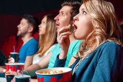 Excited woman with popcorn in cinema. Emotional film. Excited blond women eating popcorn emotionaly in cinema near other viewer royalty free stock photography