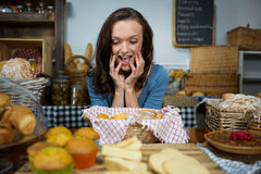 Excited woman purchasing sweet food at bakery counter stock photos