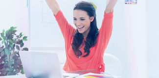 Excited woman raising her arms while working on her laptop Stock Images