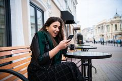 Excited woman reading amazing news on line in a smart phone at the street cafe. royalty free stock photos