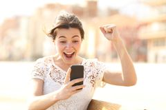 Excited woman reading amazing news on a phone stock image