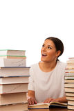 Excited woman reading behind the table between two pile of books Royalty Free Stock Photo