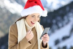 Excited woman reading on line news in christmas Stock Photo