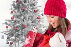 Excited woman in red beanie cap checking her christmas gifts Royalty Free Stock Photos