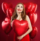 Excited woman in red dress holding balloons red heart and looking up. Surprised girl with heart on red background.