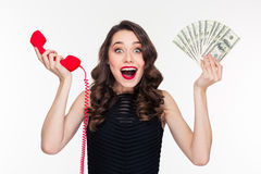 Excited woman in retro style holding money and telephone receiver Stock Photo