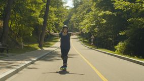Female roller enjoying extreme speed ride downhill. Excited woman rollerblading down road holding hands like wings enjoying extreme, freedom, speed on sunny stock video footage