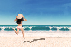 Excited woman running into the sea Stock Photography