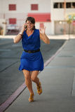 Excited woman runs and talks on cell phone. Stock Image