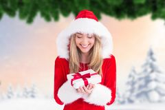 Excited woman in santa costume looking at christmas gift Stock Photography