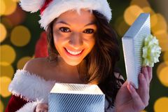 Excited woman in santa costume opening christmas gift Stock Images
