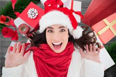 Excited woman in santa hat against digitally generated background Stock Photos