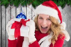 Excited woman in santa hat holding christmas gift Stock Photo