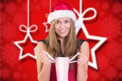 Excited woman in santa hat holding gift bag Royalty Free Stock Images