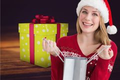 Excited woman in santa hat holding gift bag Royalty Free Stock Photography