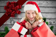 Excited woman in santa hat holding gifts during christmas time Royalty Free Stock Images
